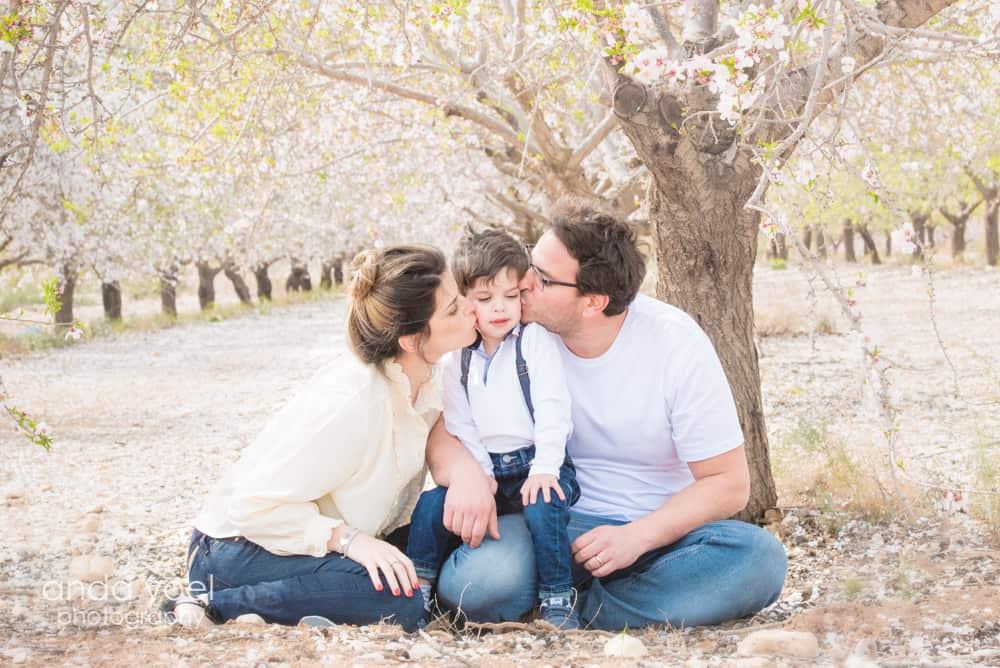 צילומי הריון ומשפחה בטבע במטע שקדיות הורים מנשקים את ילדם - אנדה יואל