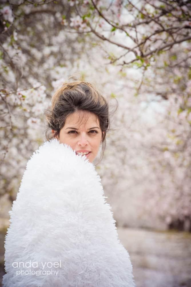 צילומי הריון ומשפחה בטבע במטע שקדיות הריונית עטופה שמיכה לבנה - אנדה יואל