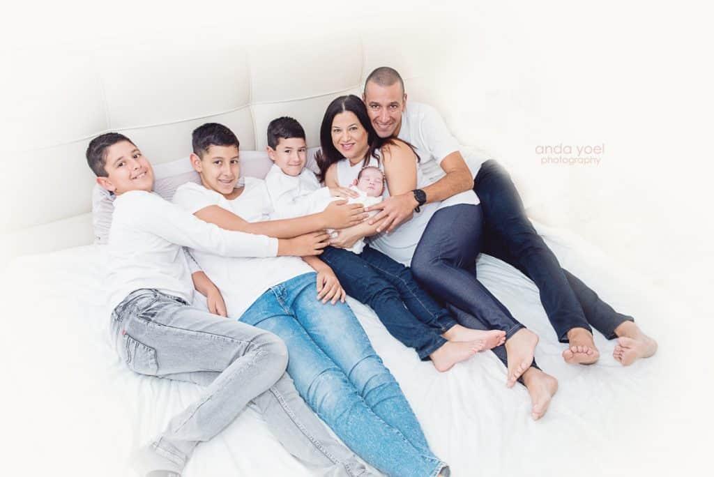 צילומי ניובורן ומשפחה בבית - כל המשפחה מחזיקה את התינוקת החדשה - אנדה יואל