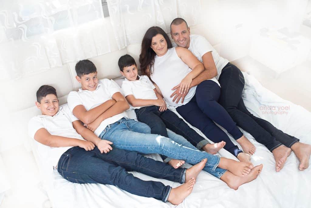 צילום הריון ומשפחה בבית - צילומי הריון בחולצה לבנה על המיטה עם הילדים - אנדה יואל