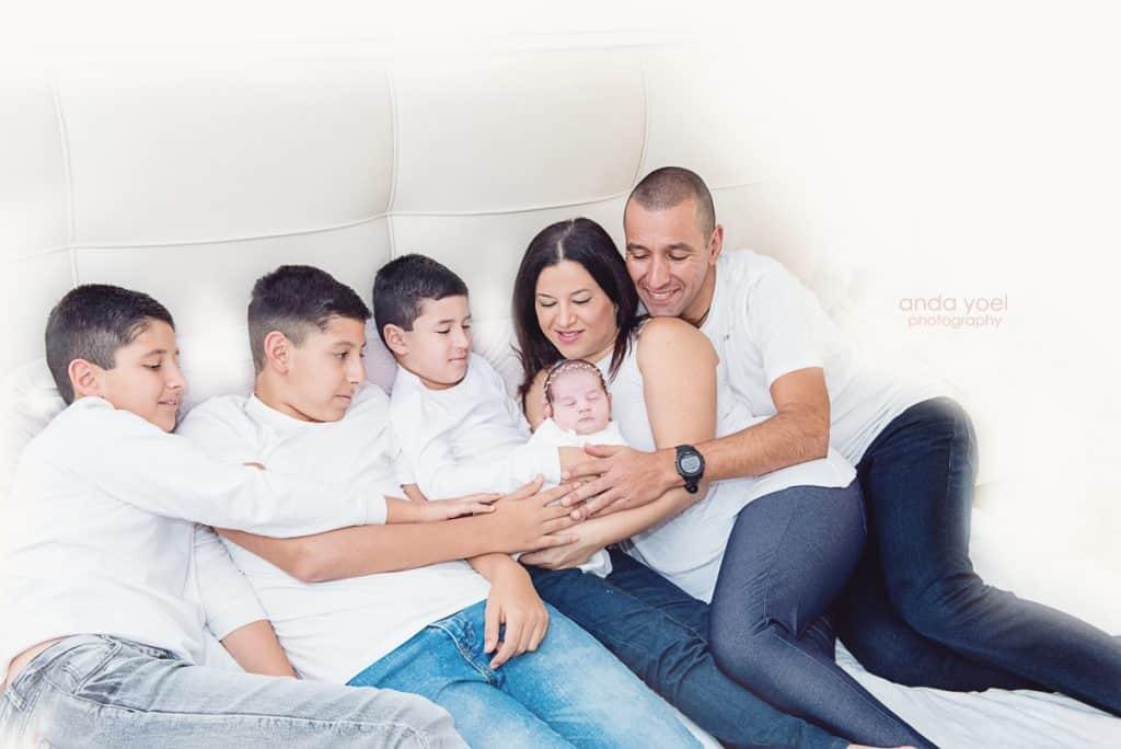 צילומי ניובורן בבית - כל המשפחה מחזיקה את התינוקת החדשה - אנדה יואל