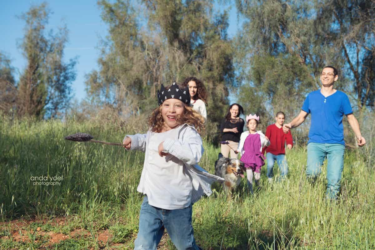 צילומי משפחה בטבע - בני המשפחה רצים בשדה אחרי ילד חייכן - אנדה יואל