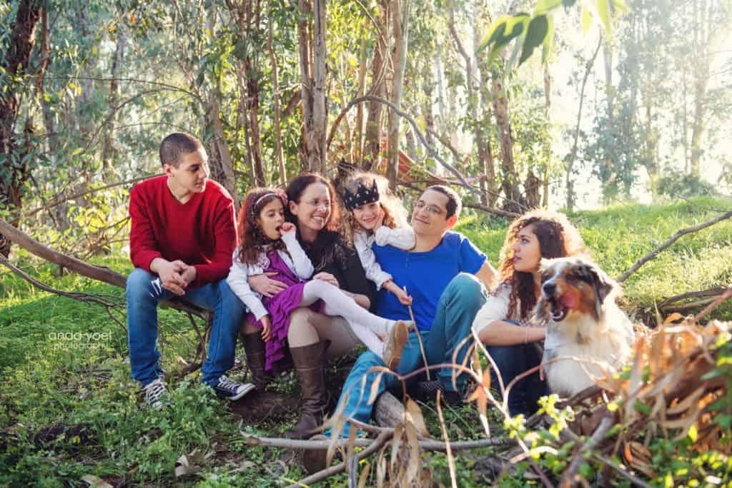 צילומי משפחה בטבע - בני המשפחה מחייכים בצילום קבוצתי עם הכלב - אנדה יואל