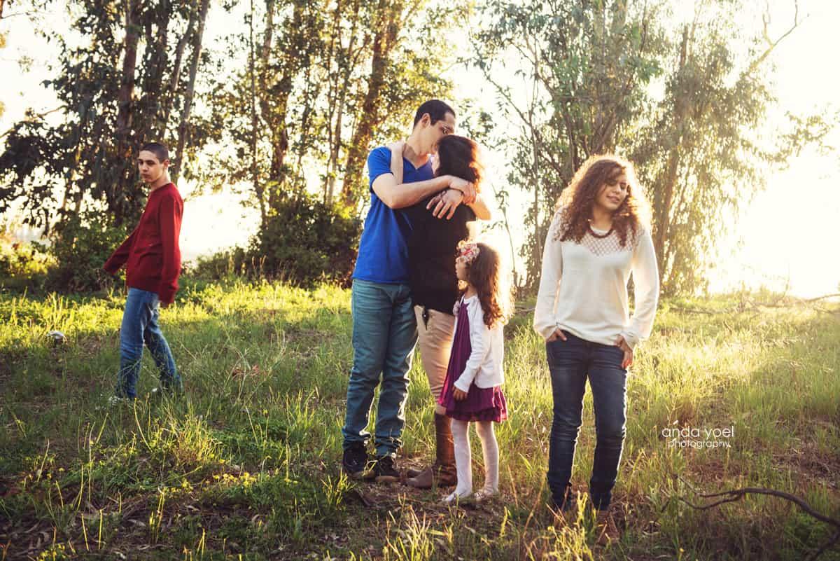צילומי משפחה בטבע - הורים מתחבקים והילדים מסתכלים הצידה - אנדה יואל