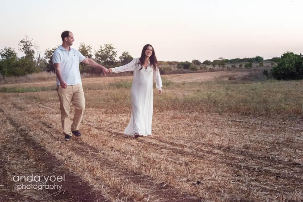 פרננדה בצילומי הריון בטבע - מחזיקים ידיים בשדה על רקע השקיעה - אנדה יואל