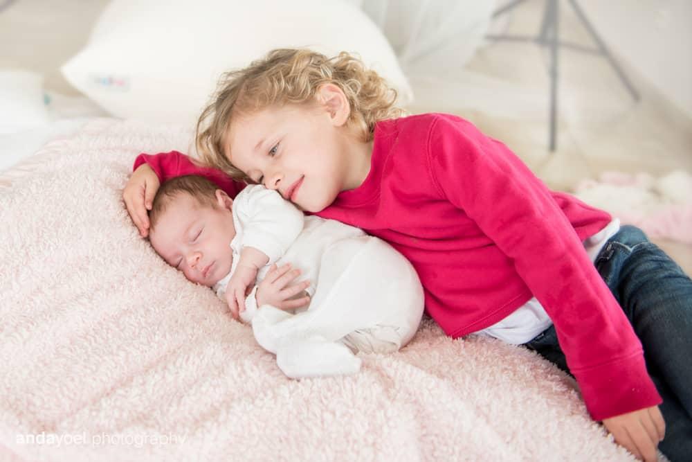 צילומי ניובורן ומשפחה לייפסטייל בבית - אחות קטנה עם התינוקת - אנדה יואל