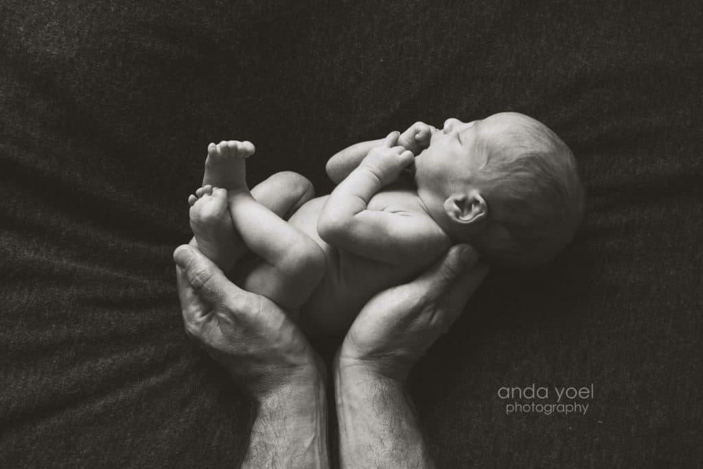 תינוק ניובורן בידיים של אבא בשחור לבן - אנדה יואל
