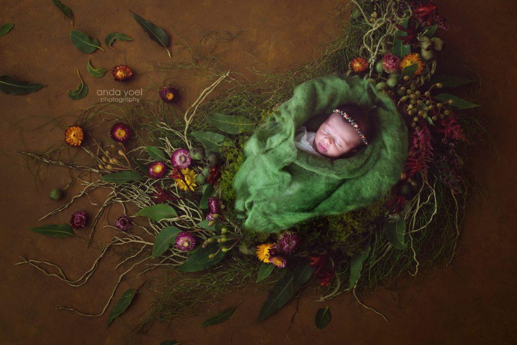 תינוקת ניובורן בעיטוף ירוק על רקע מצע של פרחים צבעוניים ועלים ירוקים - אנדה יואל