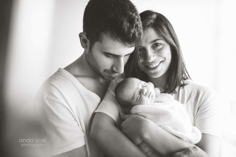 הורים מחזיקים תינוקת ניובורן - צילום בשחור לבן - אנדה יואל