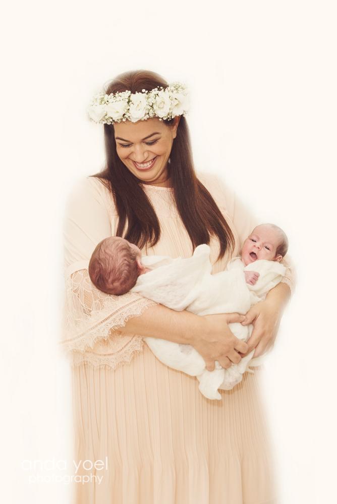 אמא מחייכת מחזיקה תינוקות ניובורן בנים תאומים בידיה - אנדה יואל