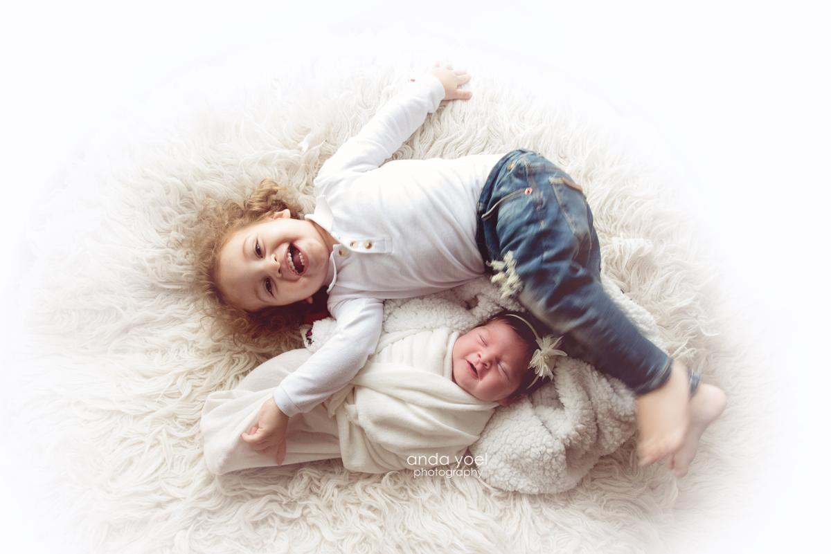 תינוקת ניובורן עם האח הגדול על פוף לבן ושניהם מחייכים - אנדה יואל