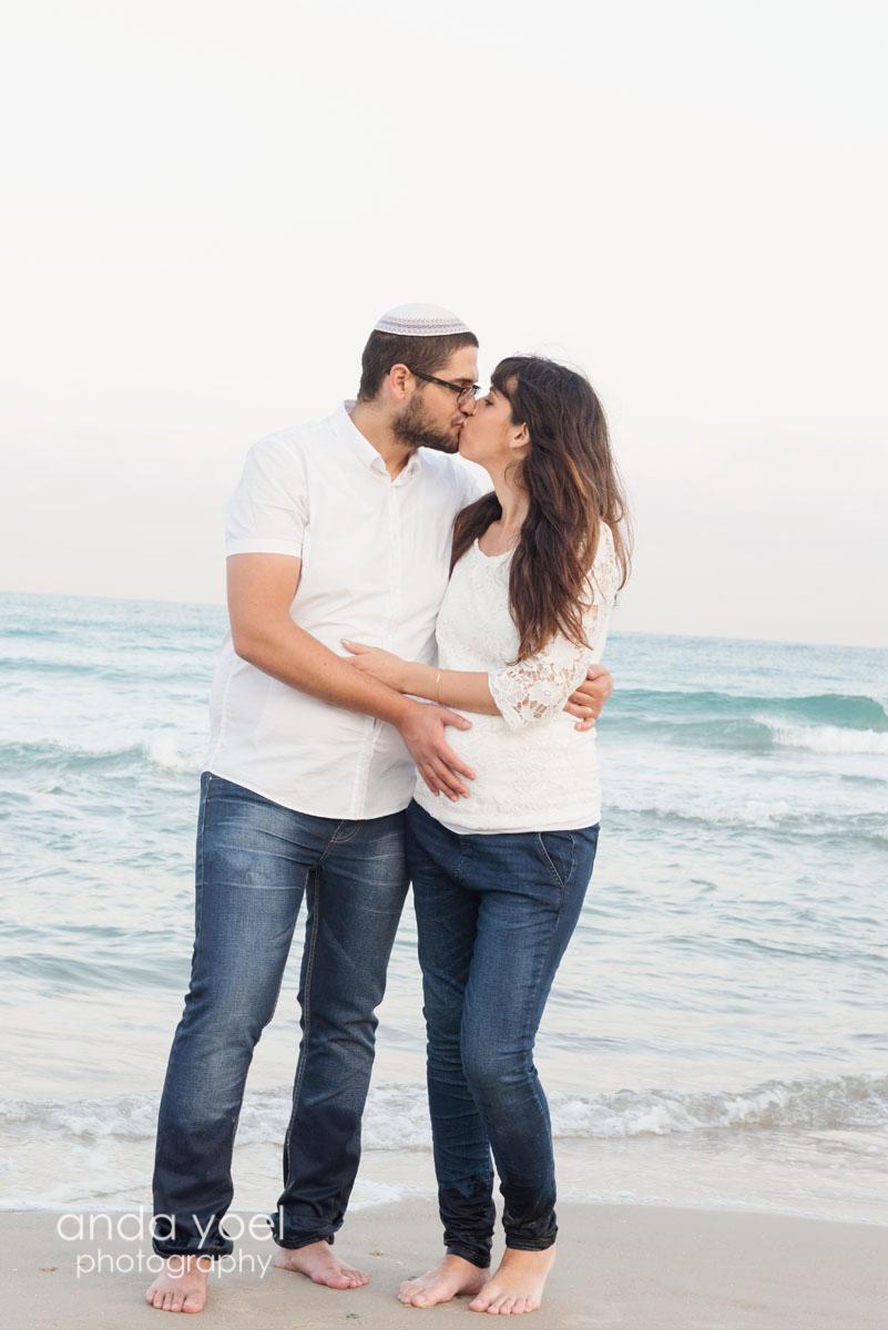 צילומי הריון צנוע - זוג הריוני בחיבוק ונשיקה על רקע הים - אנדה יואל