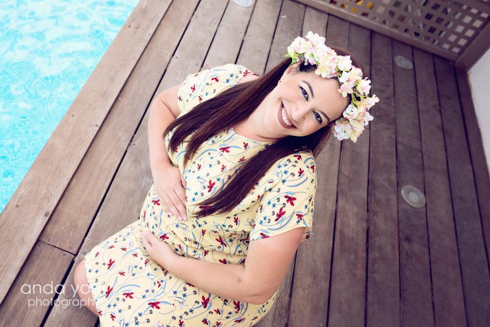 צילומי הריון צנועים - הריונית בשמלה פרחונית על רקע דק עץ בבריכה - אנדה יואל
