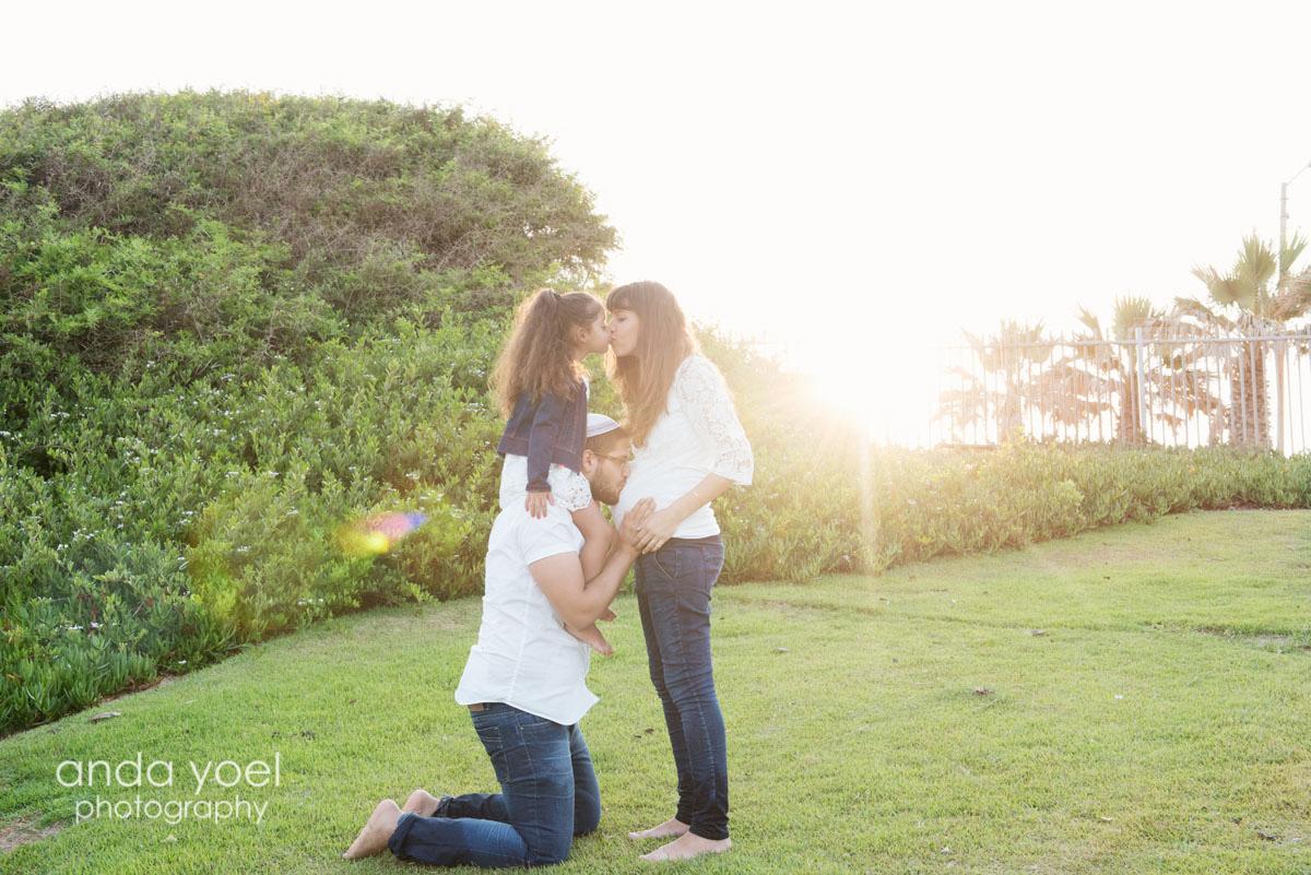 צילומי הריון צנוע - זוג הריוני מחובק, בתם נותנת נשיקה לאמא על רקע צמחיה ירוקה - אנדה יואל