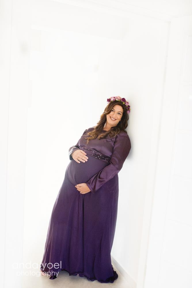 צילומי הריון צנוע - הריונית בשמלה סגולה עם זר אדום על ראשה מביטה למצלמה - אנדה יואל