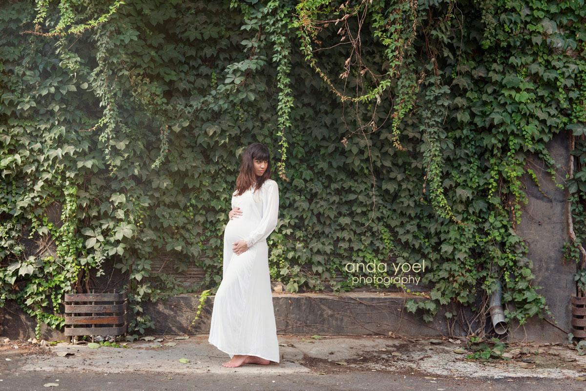 צילום הריון צנוע - הריונית בשמלה לבנה ארוכה מביטה לאחור על רקע צמחיה ירוקה - אנדה יואל