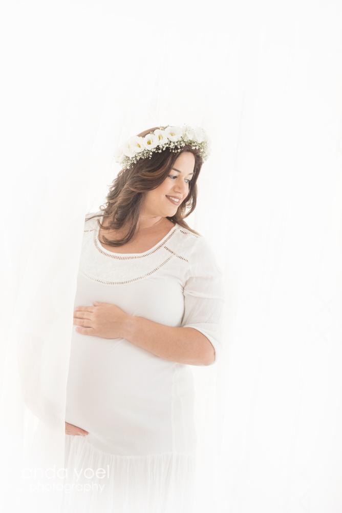 צילומי הריון צנוע - הריונית בשמלה בצבע לבן וזר לבן טבעי מביטה הצידה על רקע לבן בוהק - אנדה יואל