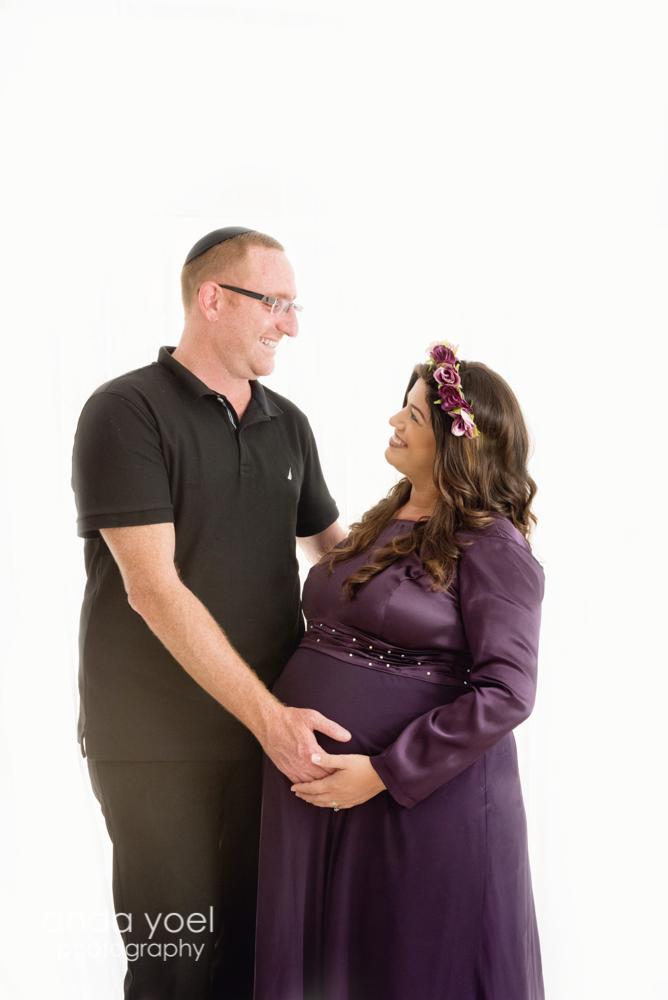 צילומי הריון צנוע בזוג - הריונית בשמלה סגולה מביטה על בן הזוג על רקע לבן - אנדה יואל