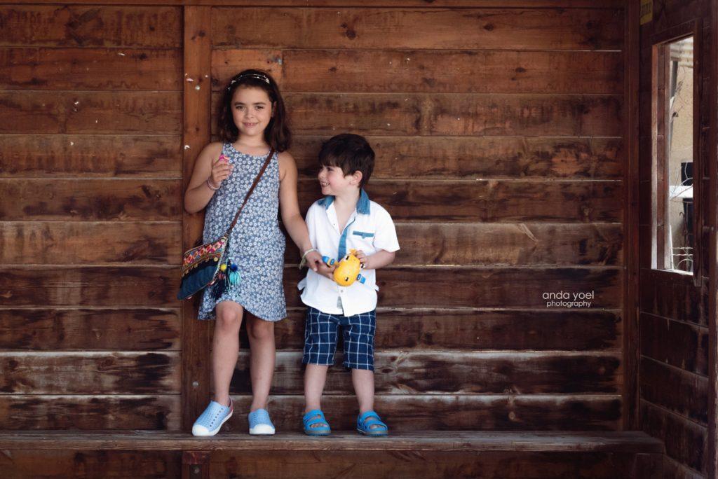 צילומי ילדים ומשפחה בטבע - משפחת שדה - יאח ואחות על רקע קיר עץ - אנדה יואל