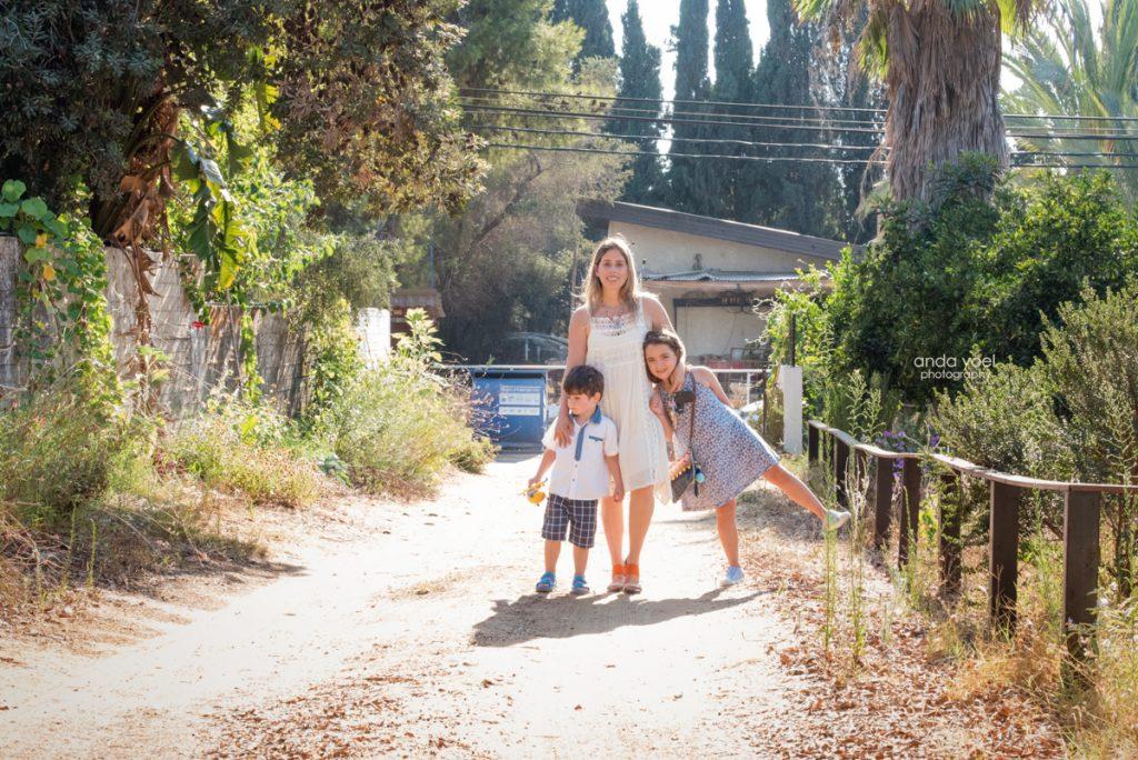 צילומי ילדים ומשפחה בטבע - משפחת שדה - אמא וילדיה מחובקים על רקע שביל עפר - אנדה יואל