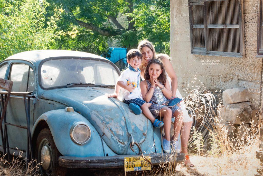 צילומי ילדים ומשפחה בטבע - משפחת שדה - אמא והילדים מחובקים על רקע חיפושית תכלת - אנדה יואל