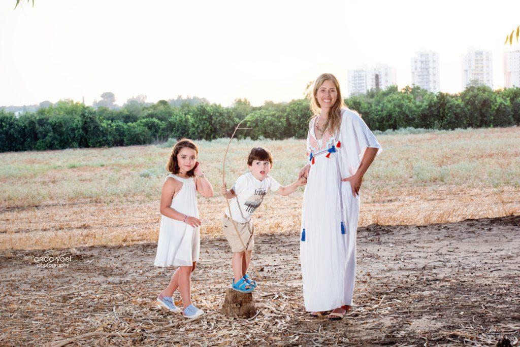 צילומי ילדים ומשפחה בטבע - משפחת שדה - אמא וילדיה מחזיקים ידיים בשדה - אנדה יואל
