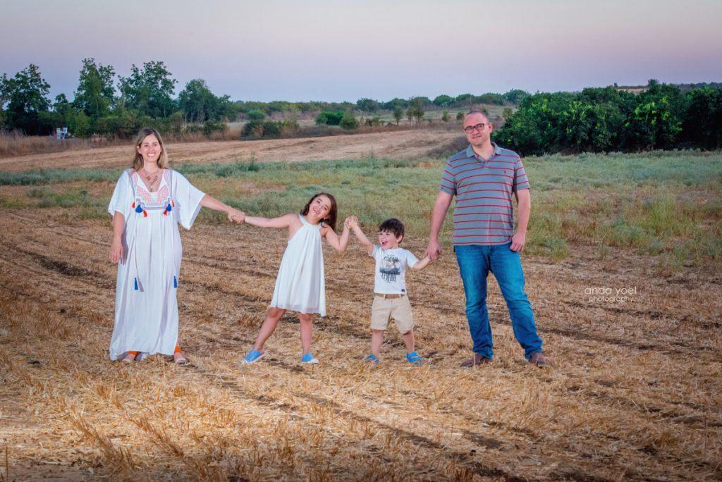 צילומי ילדים ומשפחה בטבע - משפחת שדה- משפחה מחזיקה ידיים בשדה - אנדה יואל