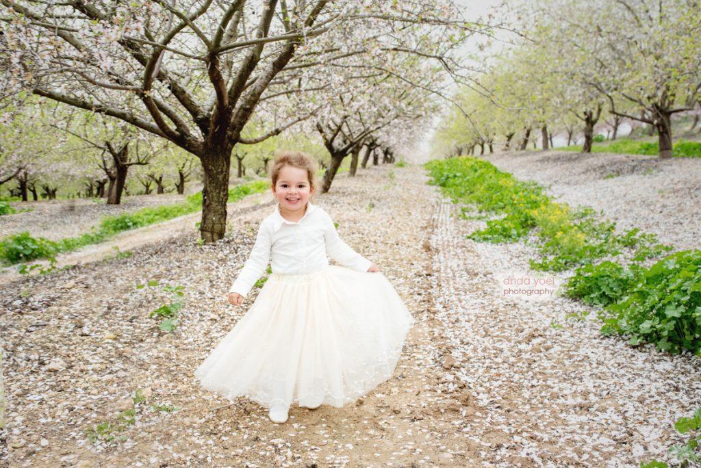 צילומי ילדים ומשפחה בטבע - ילדה רוקדת במטע שקדיות - אנדה יואל