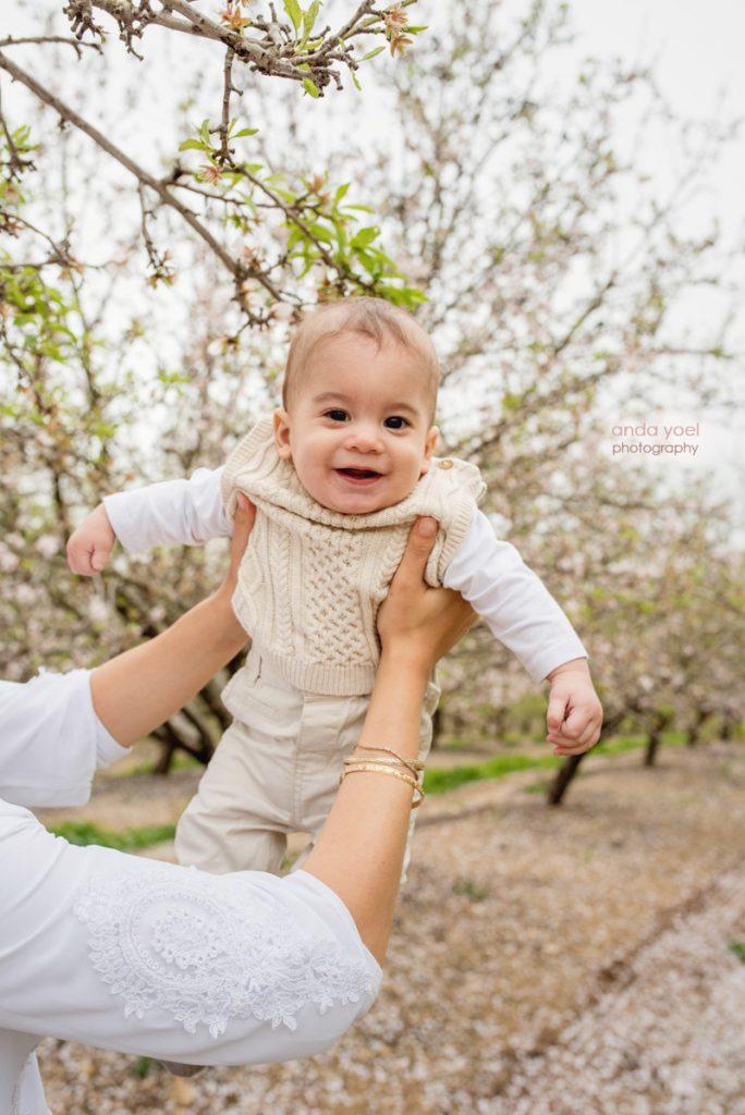 צילומי ילדים ומשפחה בטבע במטע שקדיות - ההורים מחזיקים את התינוק על רקע מטע פורח - אנדה יואל