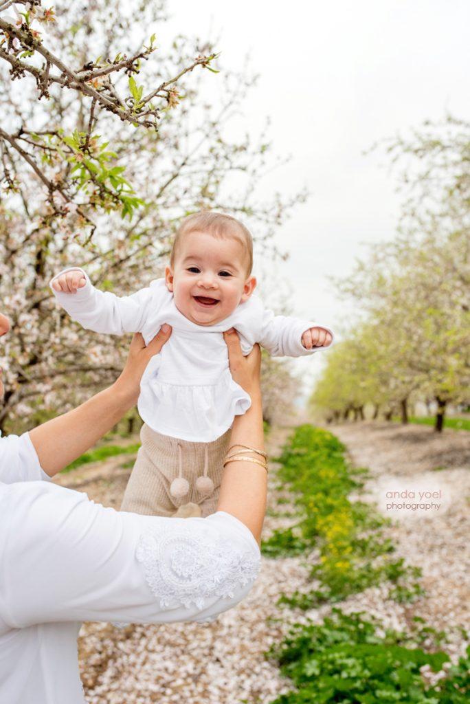 צילומי ילדים ומשפחה בטבע - ההורים מחזיקים את התינוקת על רקע מטע פורח - אנדה יואל