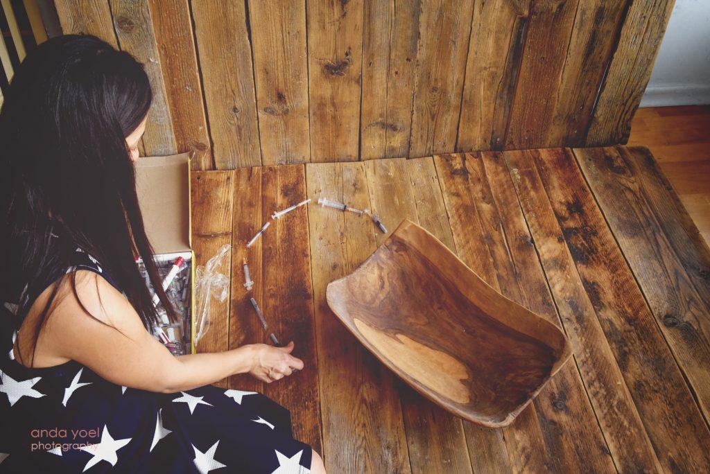 אמא שילדה לאחר טיפולי פוריות מסדרת את במזרקים של הטיפולים בצורת לב - צילום אנדה יואל