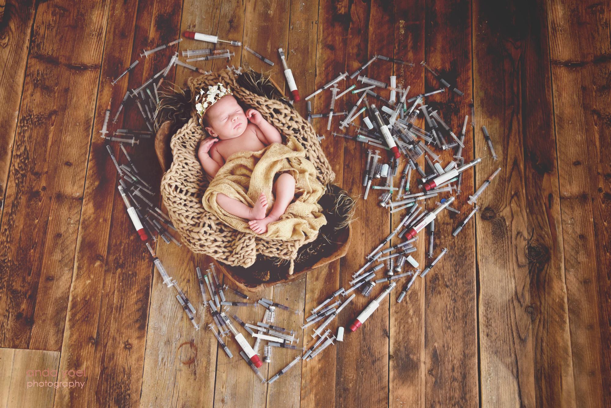תינוקת ניובורן שנולדה לאחר טיפולי פוריות ישנה בתוך סריג חום ליד מזרקי טיפולי הפוריות - צילום אנדה יואל