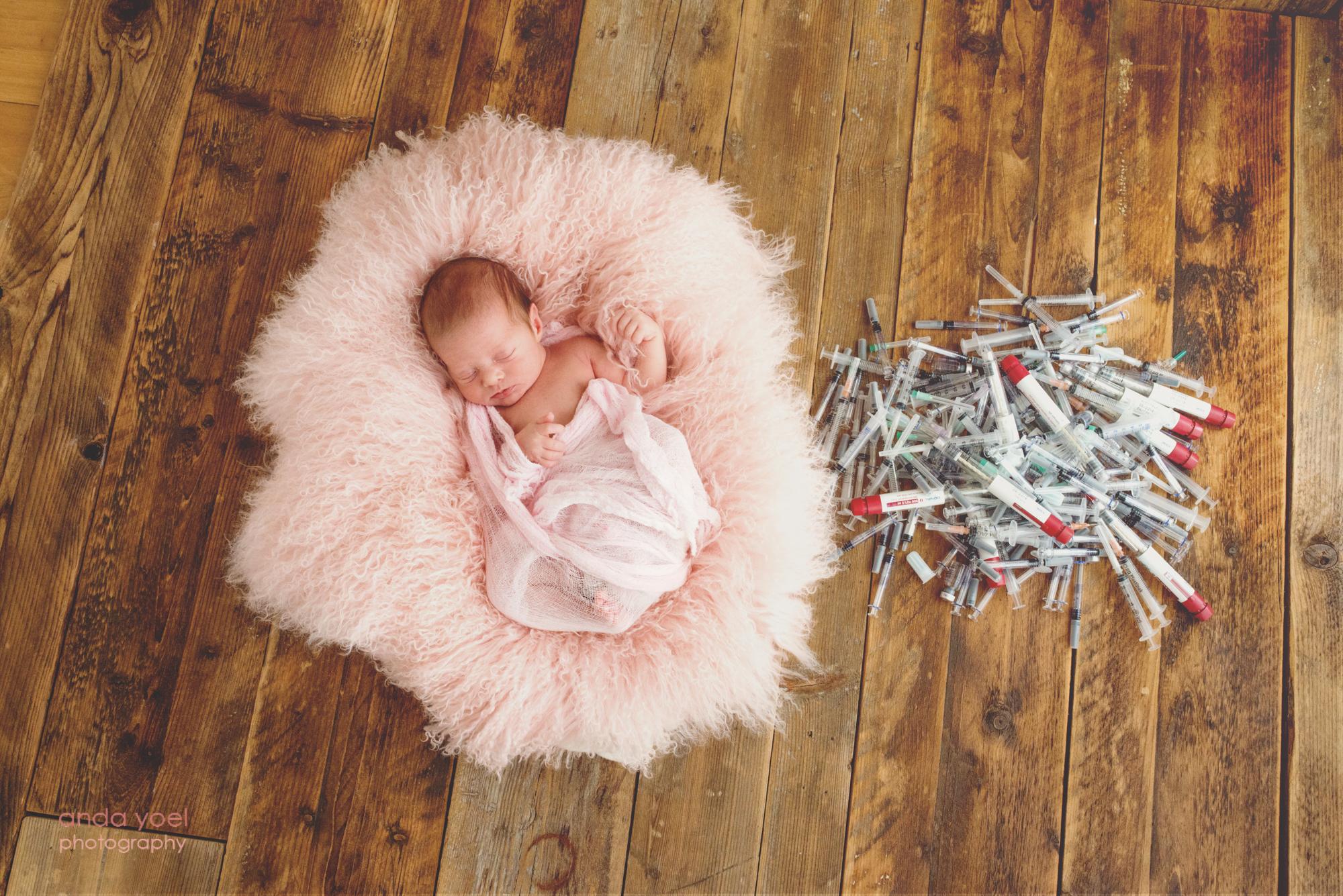 תינוקת ניובורן שנולדה לאחר טיפולי פוריות ישנה בתוך פרווה נעימה ורודה ליד מזרקי טיפולי הפוריות - צילום אנדה יואל