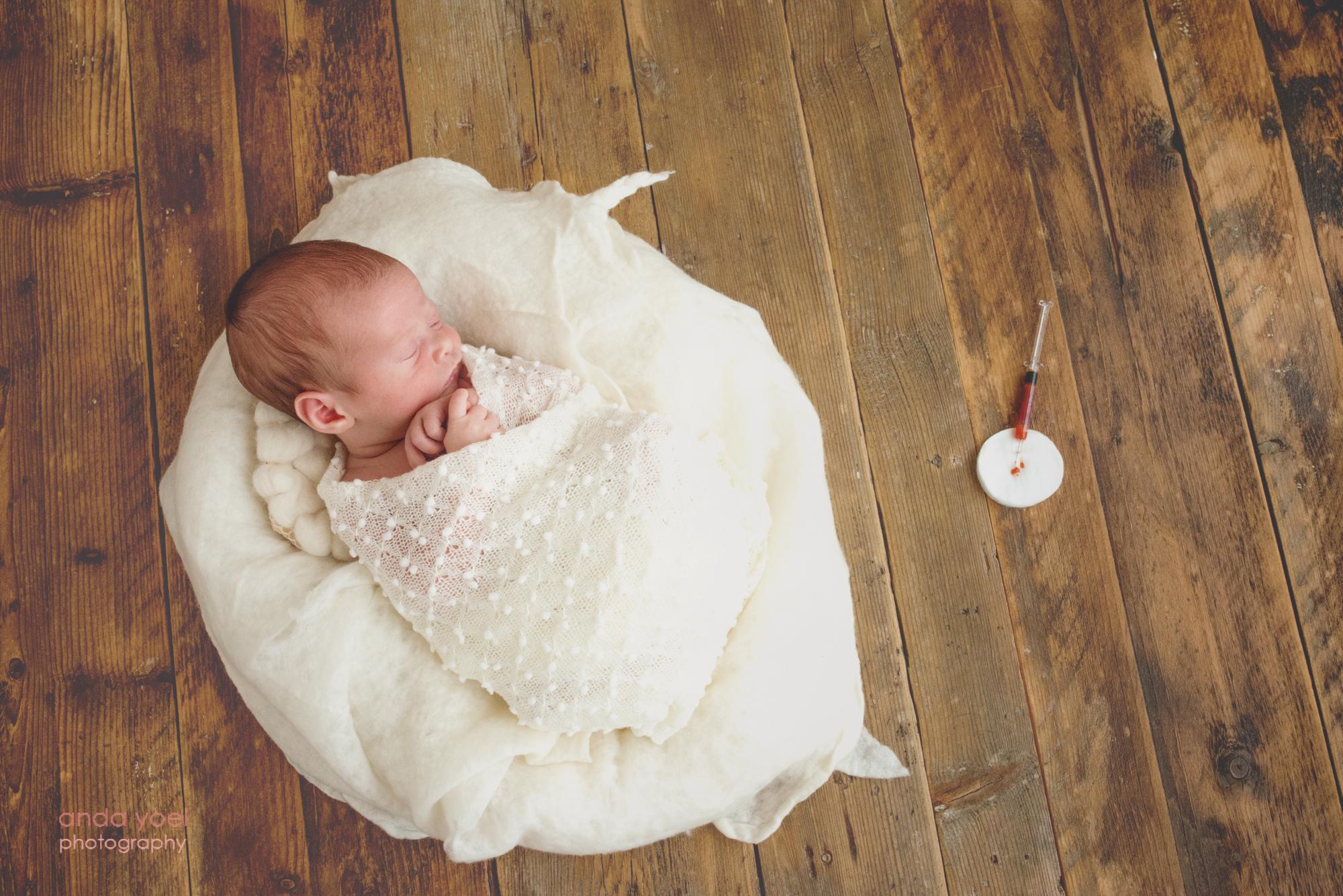 תינוקת ניובורן ליד מזרק שמדמה את טיפולי הפוריות של האמא לפני שנכנסה להריון אחרי טיפולי פוריות - צלמת אנדה יואל