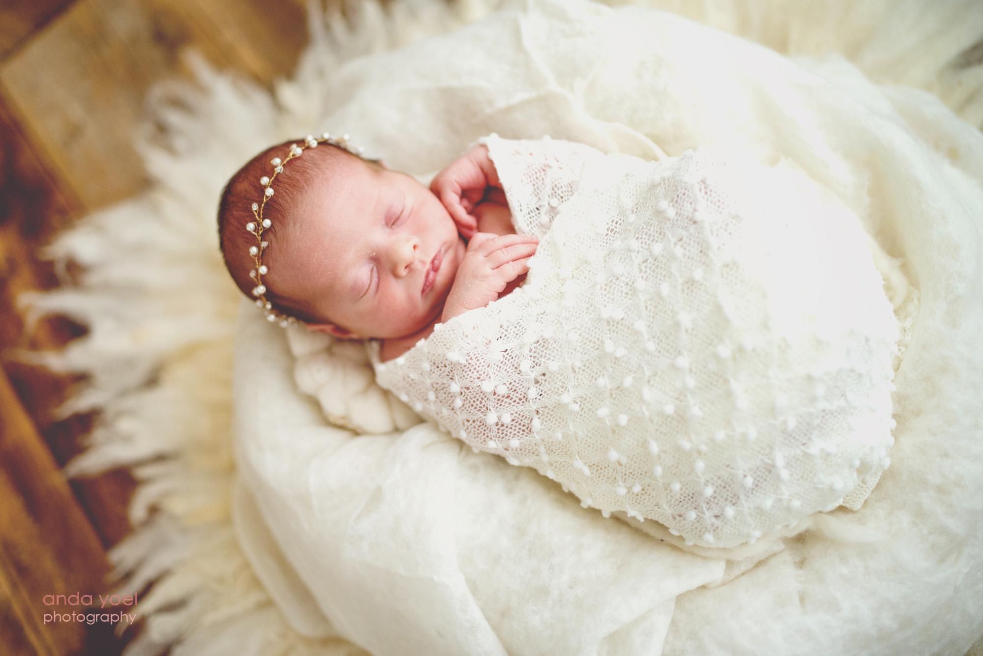 2תינוקת ניו בורן עטופה עיטוף לבן על רקע כרית לבנה - צילום אנדה יואל