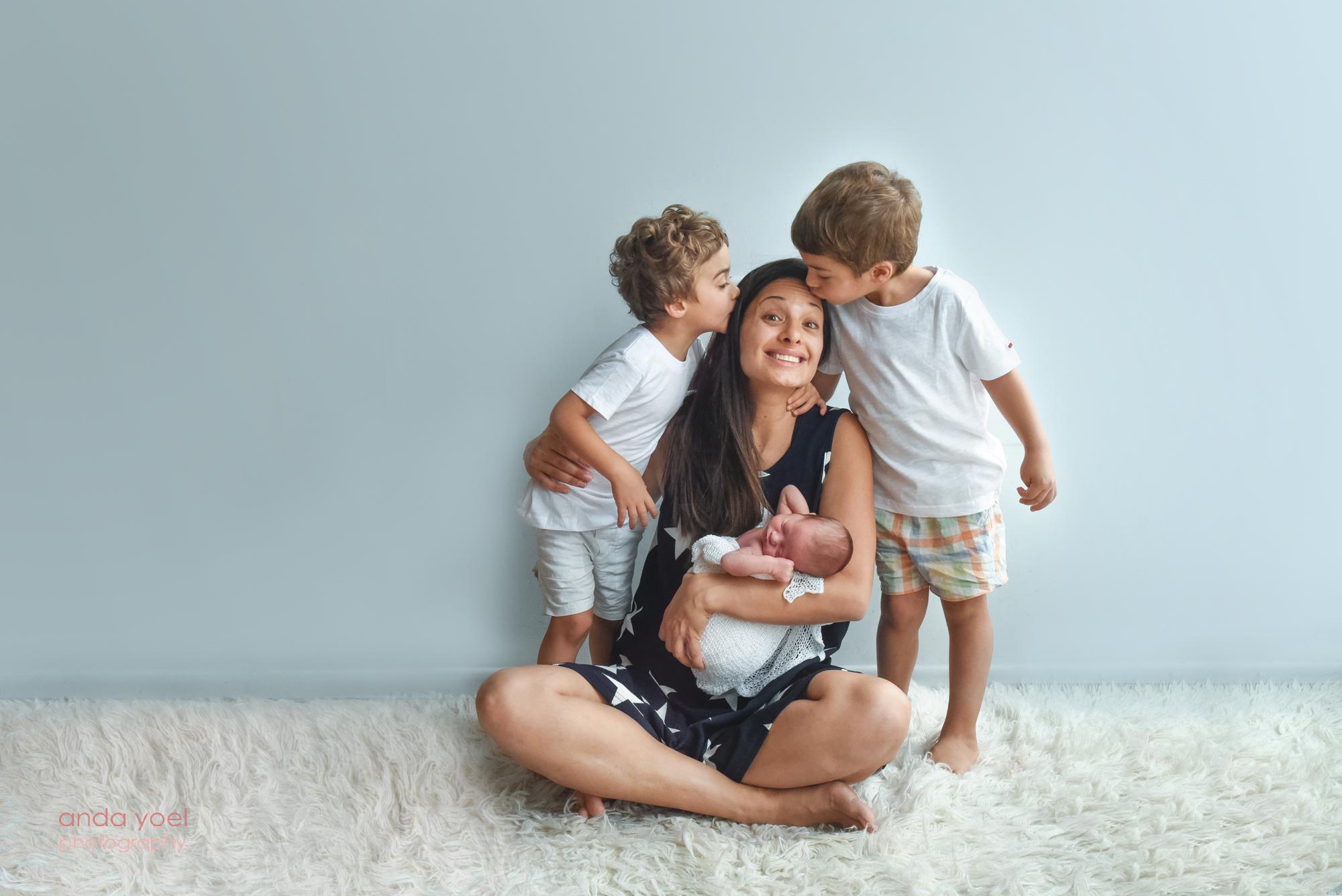 אמא מחזיקה תינוקת ושני בניה נותנים לה נשיקה