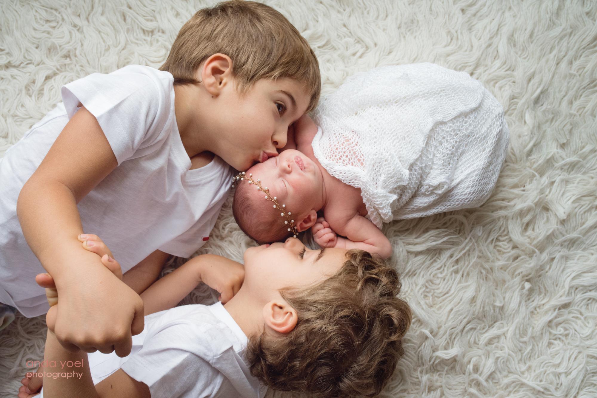 אחים תאומים מנשקים את האחות התינוקת - צילומי ניובורן אחרי טיפולי פוריות