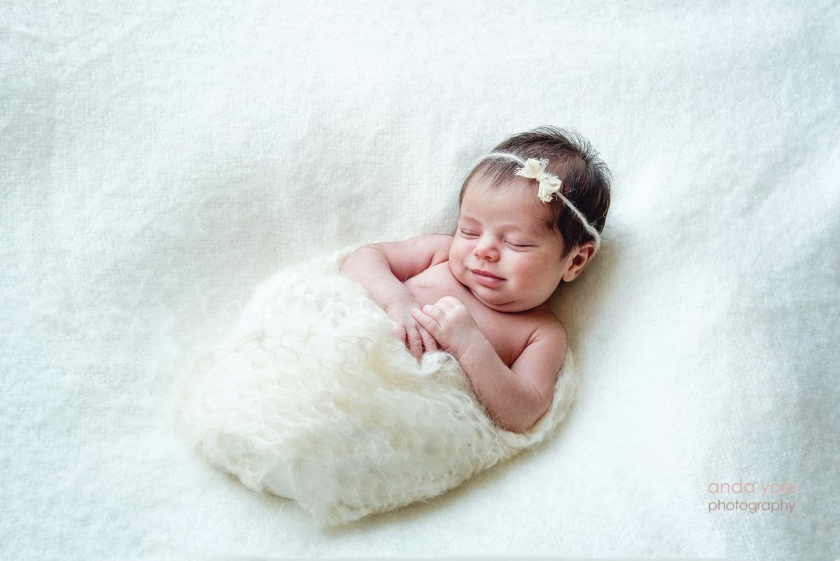צילומי ניובורן בסגנון טבעי תינוקת עם סרט לראשה מחייכת על רקע לבן ונקי - אנדה יואל