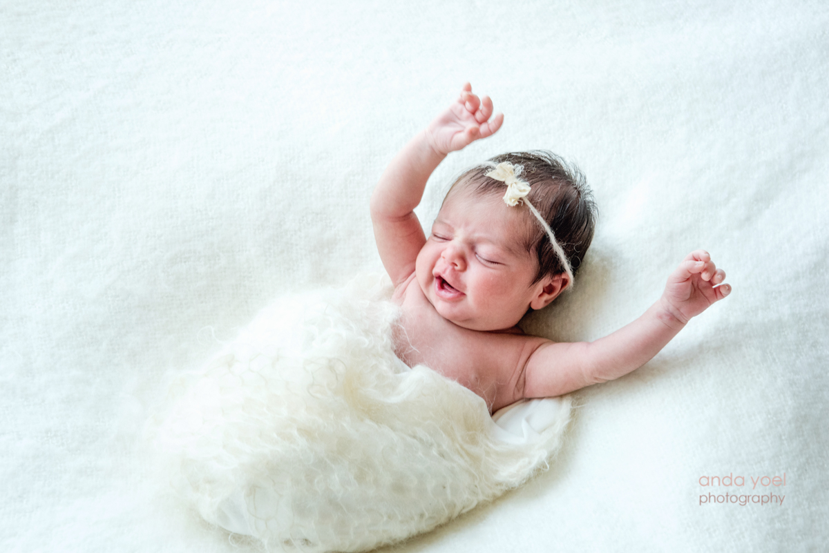 צילומי ניובורן בסגנון טבעי תינוקת עם סרט לראשה על רקע לבן ונקי - אנדה יואל