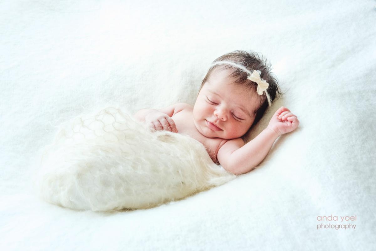 צילומי ניובורן בסגנון טבעי תינוקת מחייכת בשנתה - אנדה יואל