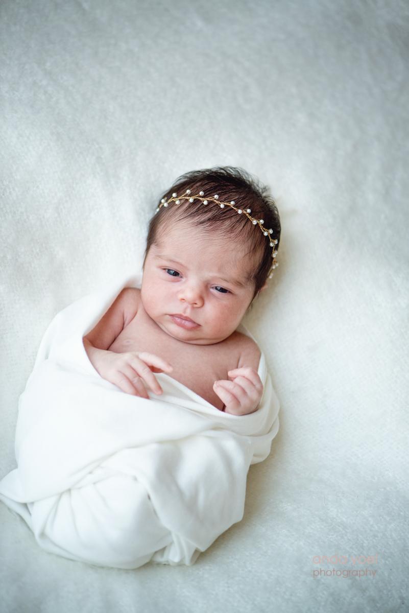 צילומי ניובורן בסגנון טבעי תינוקת עם כתר פנינים על רקע לבן ונקי - אנדה יואל