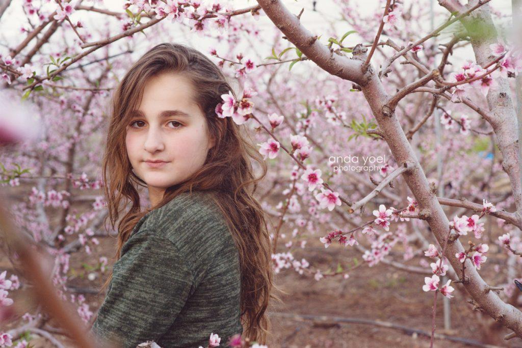 ילדה במבט למצלמה במטע שקדיות - אנדה יואל