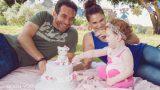 תינוקת בת שנה עם ההורים ועוגת יום הולדת בצילומי גיל שנה בטבע מסדרת הצילומים של אנדה יואל