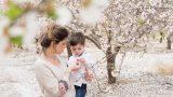 צילומי הריון ומשפחה בטבע במטע שקדיות הריונית נותנת פרח שקדיות לבנה - אנדה יואל